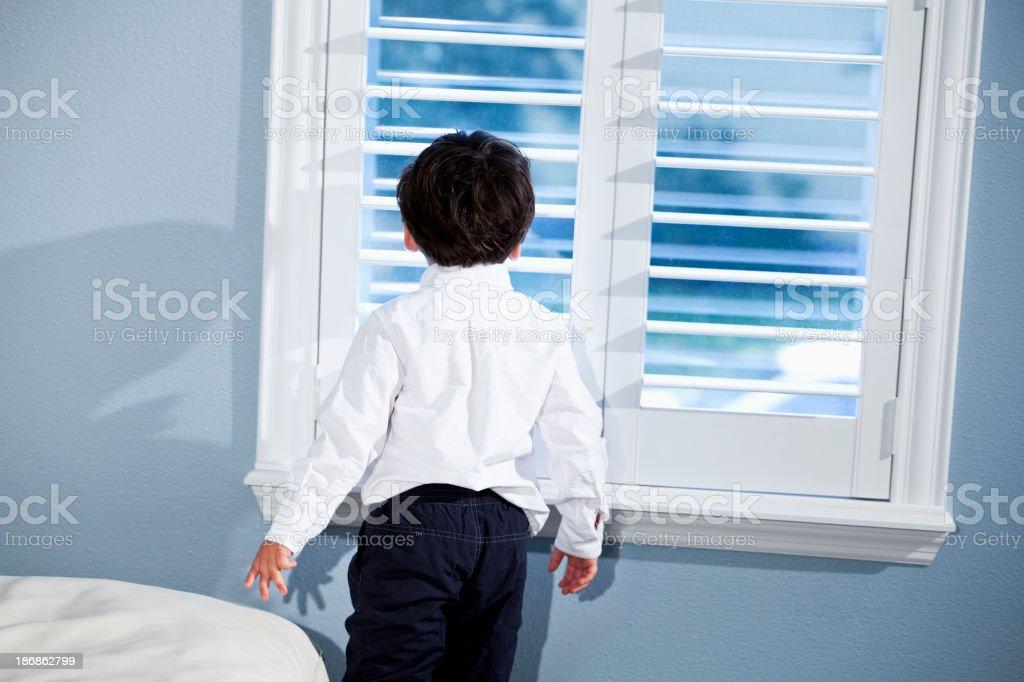 Little boy looking out window stock photo