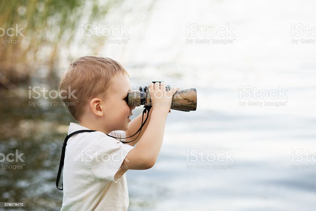 Little boy looking through binoculars on river bank stock photo