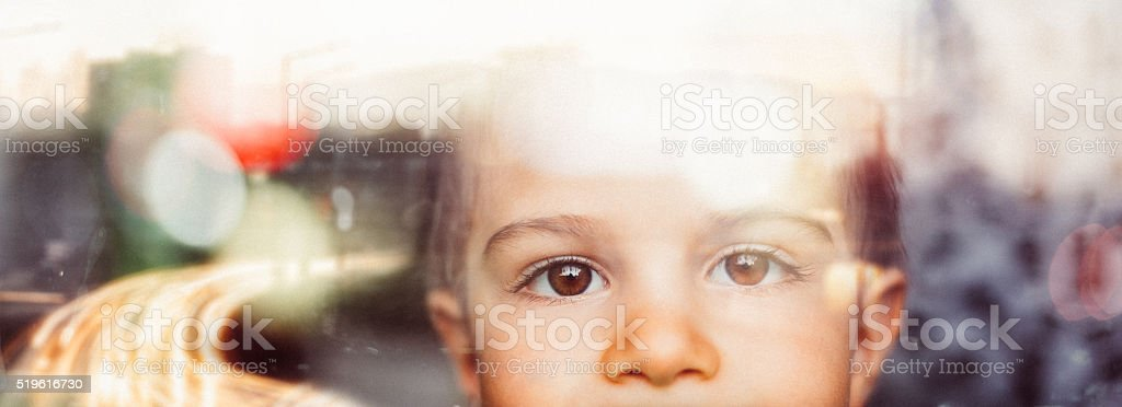 Little boy looking through the window stock photo
