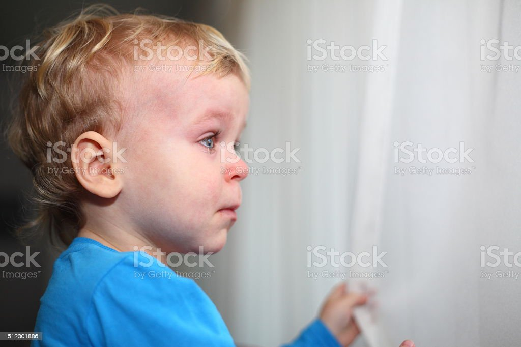 Little boy looking through window and crying stock photo