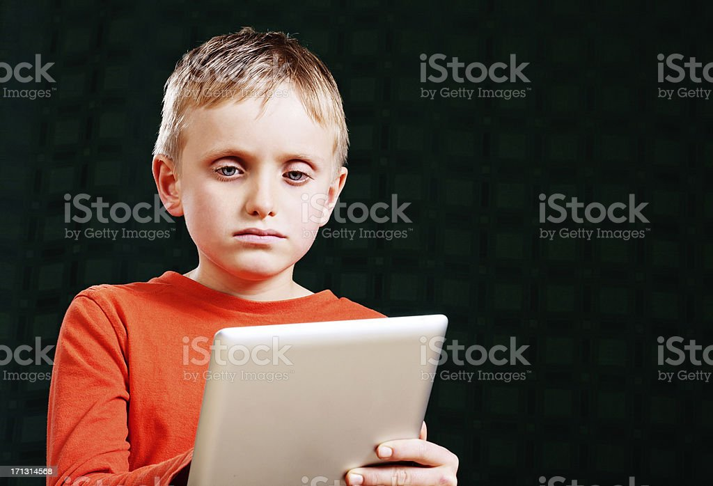 Little boy looks at digital tablet screen, bored or confused royalty-free stock photo