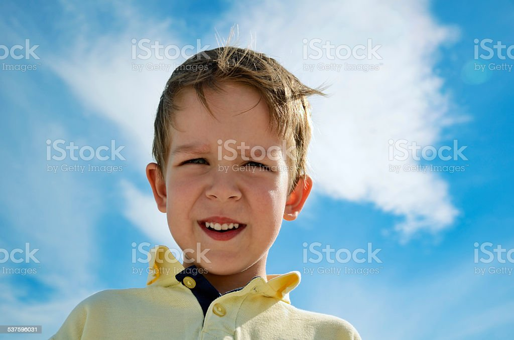 little boy looks down on blue sky background horizontal stock photo