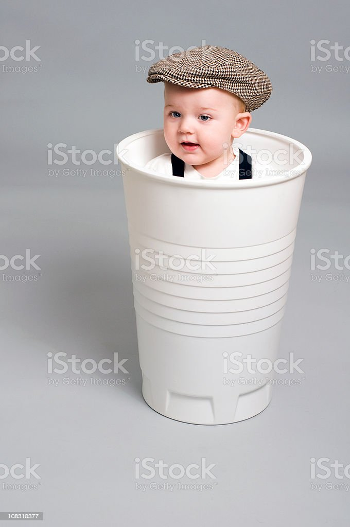 Little boy looks up from a gigant plastic cup stock photo