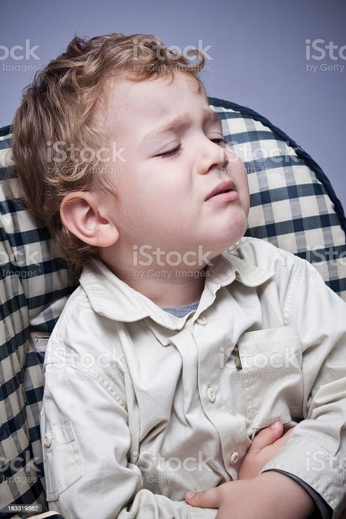 Little boy looks upset while holding his tummy royalty-free stock photo