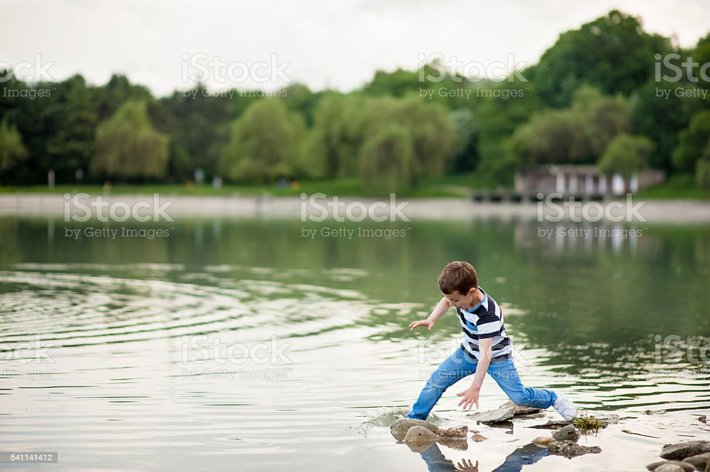 little boy lost his balance and went into the lake stock photo