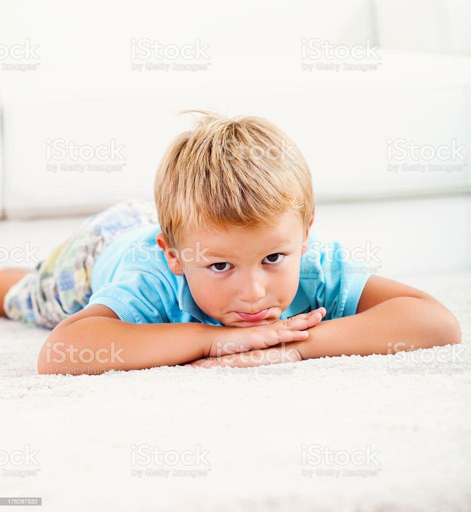 Little boy lying down on white carpet living room floor royalty-free stock photo