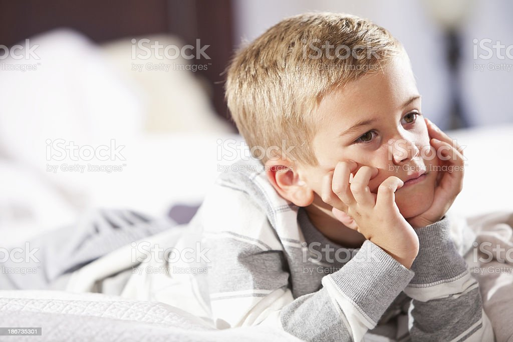 Little boy lying on bed daydreaming stock photo