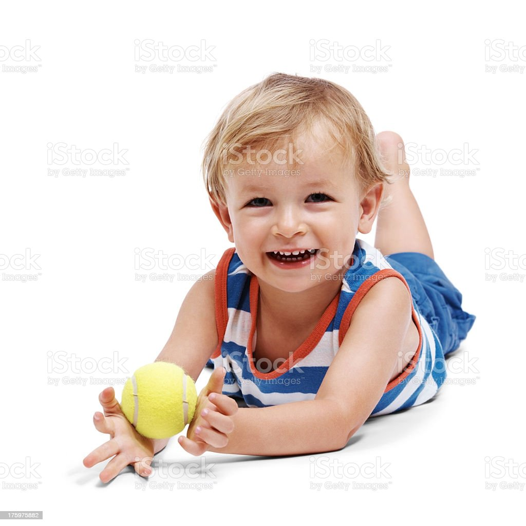 Little boy lying on floor with tennis ball royalty-free stock photo