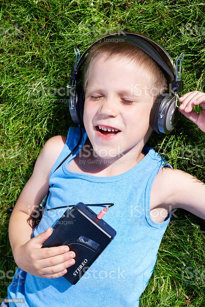 Little boy lying on grass with old audio cassette player stock photo