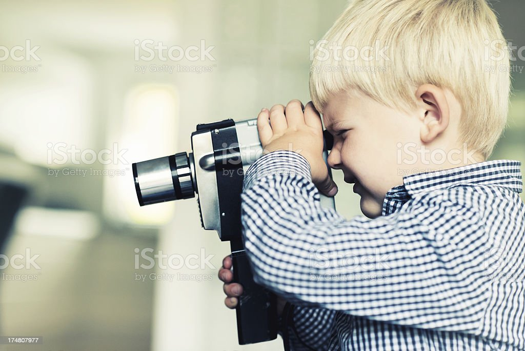 Little boy makes a video with an old retro camera royalty-free stock photo
