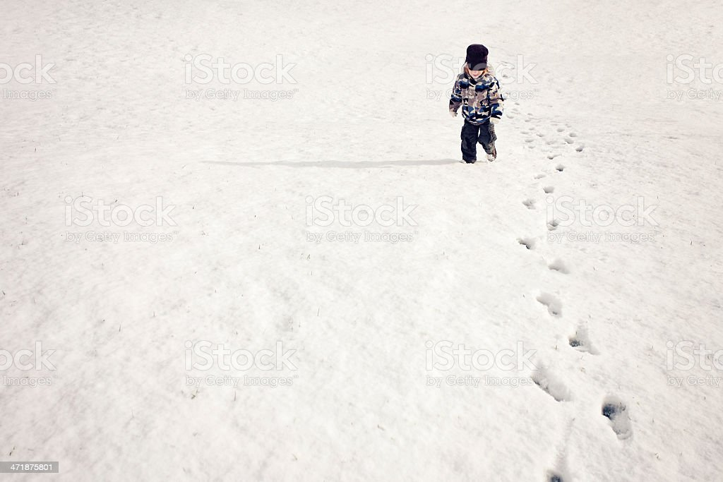 Little boy making footprints in the snow stock photo