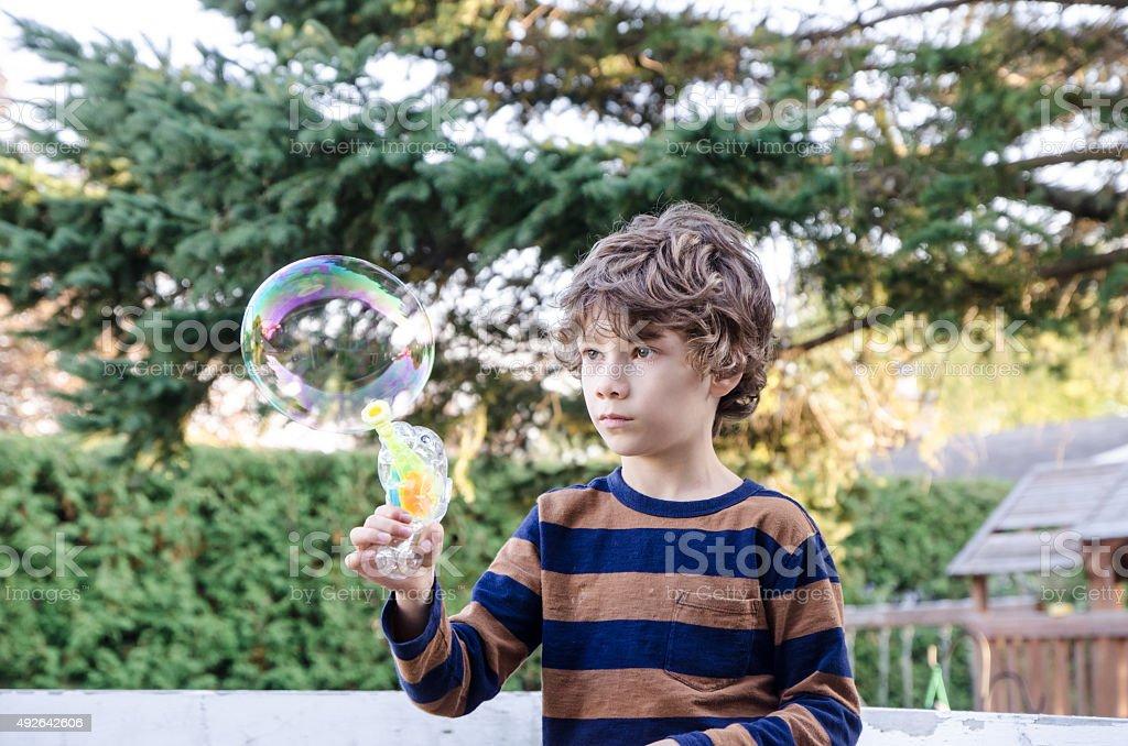 Little boy making soap bubble outside stock photo
