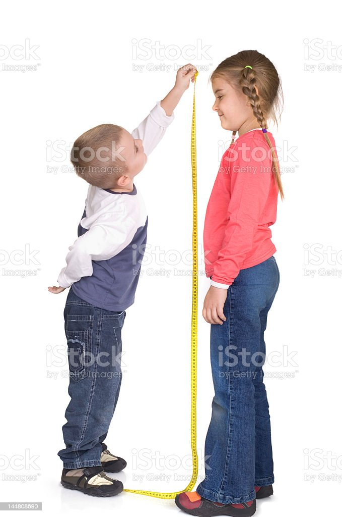 Little boy measuring the height of a slightly taller girl stock photo