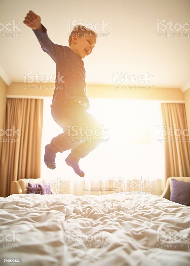 Little boy mid air jumping with joy on bed. stock photo