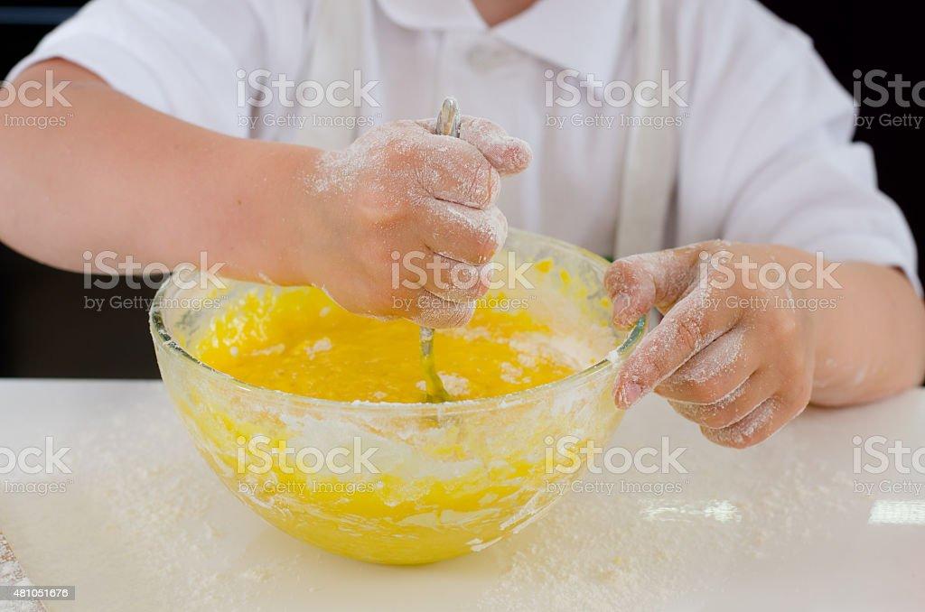 Little boy mixing cake ingredients stock photo