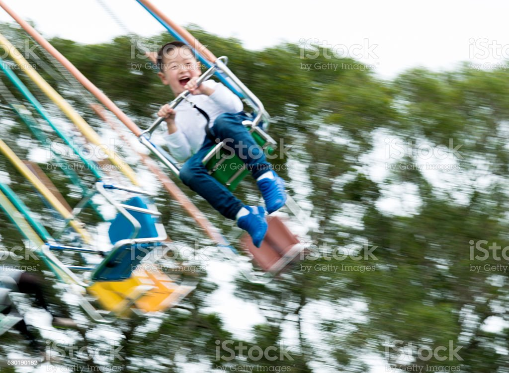Little boy on a swinging ride stock photo