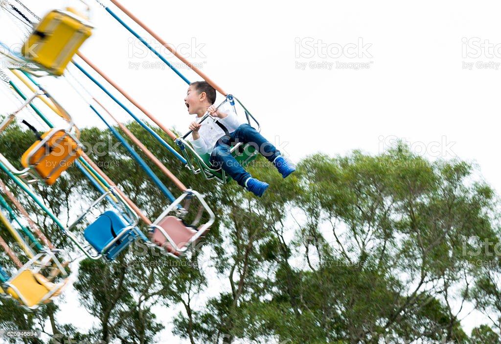 Little boy on a swinging ride stock photo