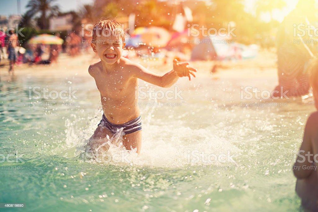 Little boy on beach having fun in sea splashing stock photo