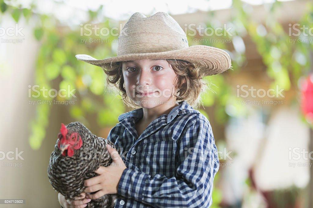 Little boy on farm holding a chicken stock photo
