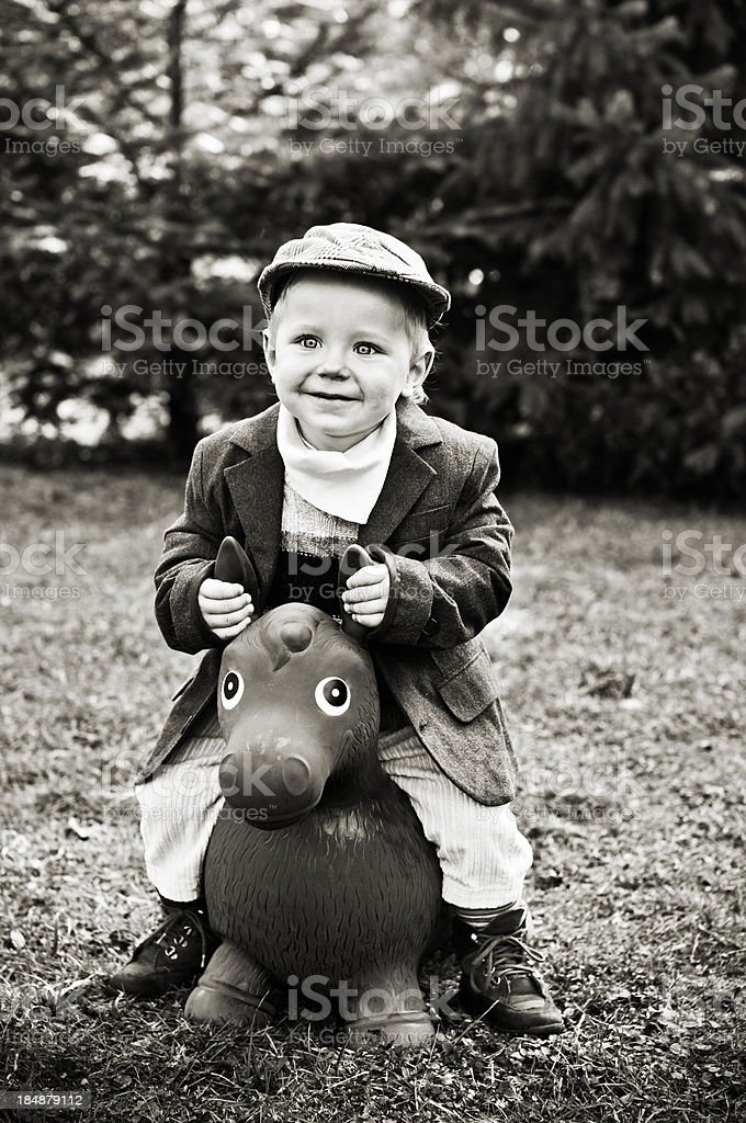 Little boy on horse toy stock photo