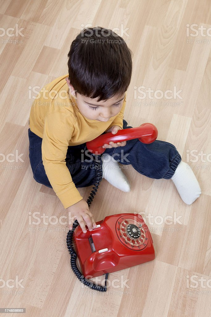 little boy on phone with hat stock photo