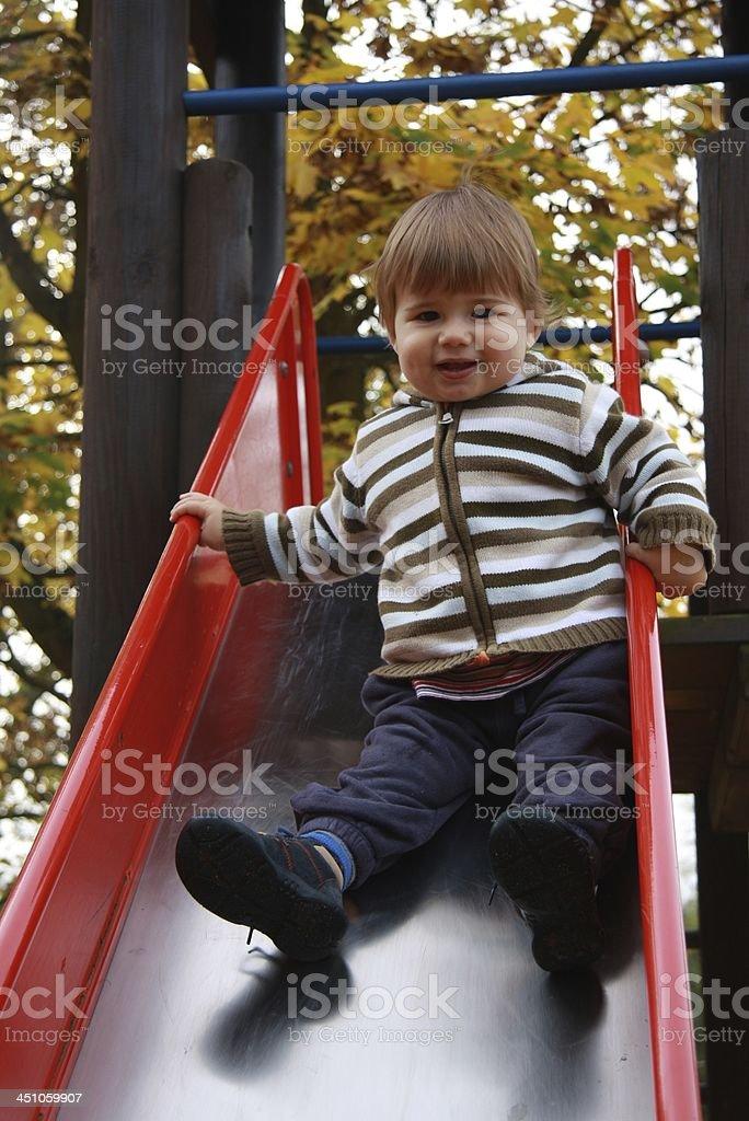 little boy on the playground in autumn stock photo