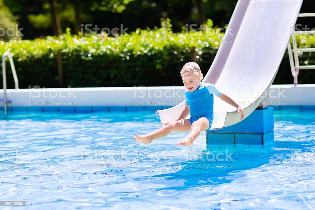 Little boy on water slide in swimming pool stock photo