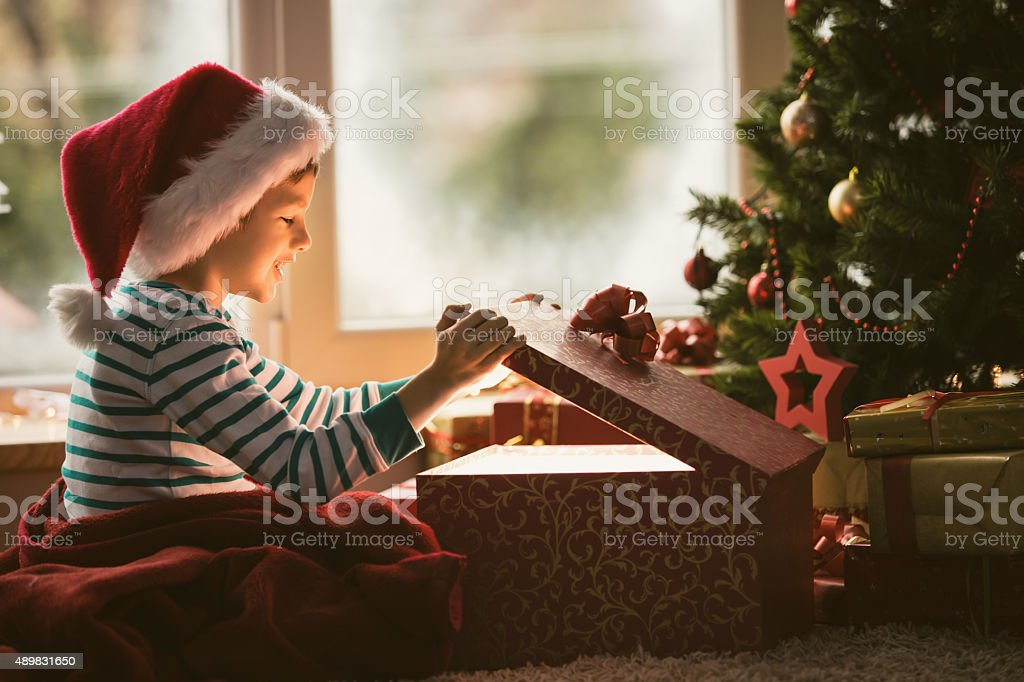 Little boy opening Christmas present stock photo
