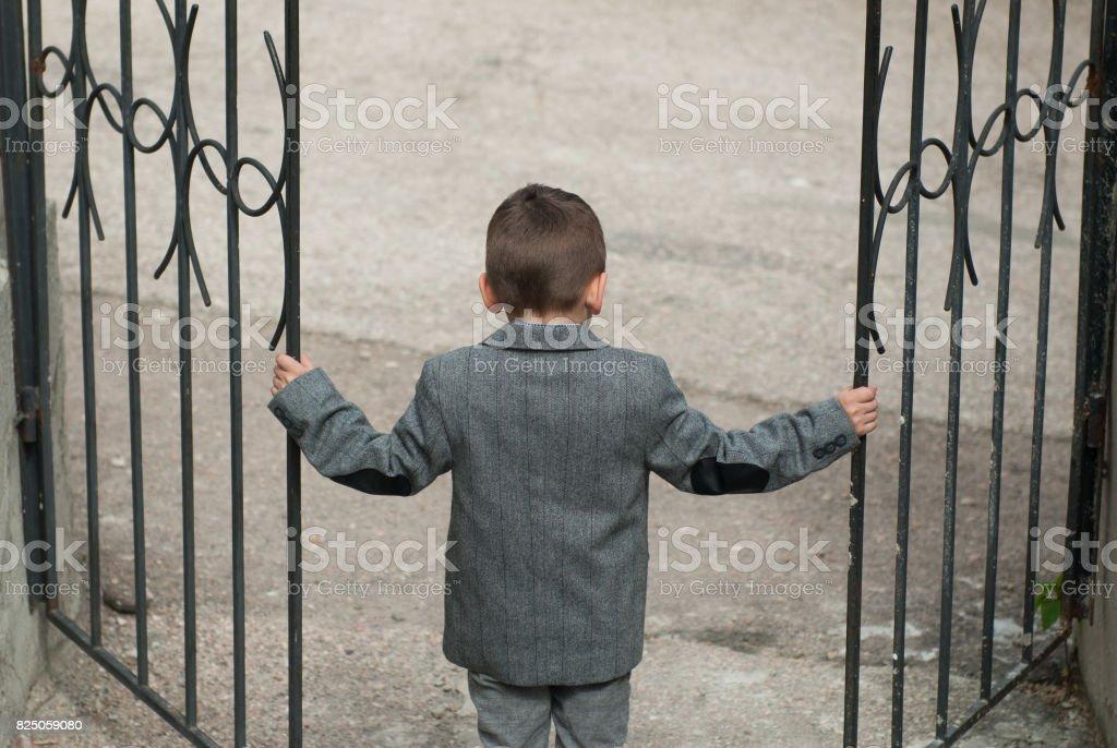 Little boy opens a wrought-iron gate stock photo