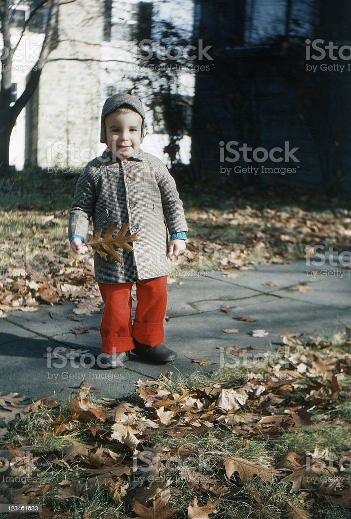 little boy outdoors in coat and hat autumn 1955, retro stock photo