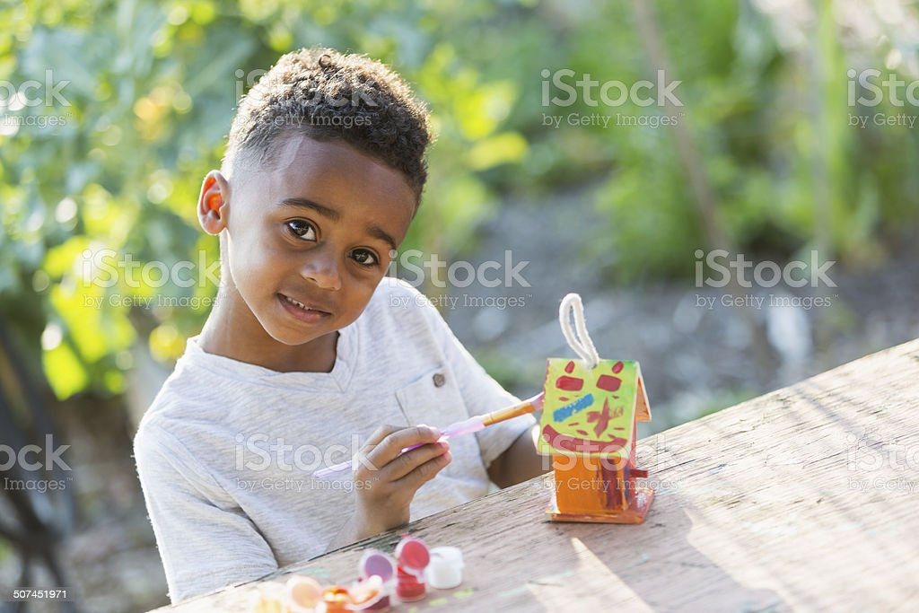 Little boy painting bird house stock photo