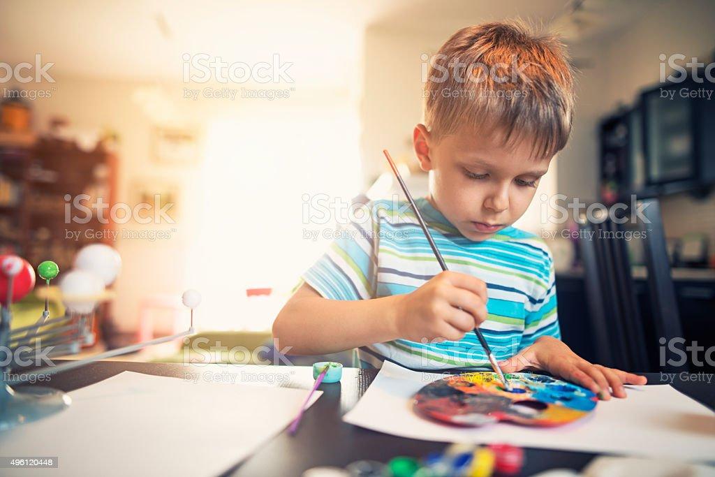 Little boy painting solar system model stock photo