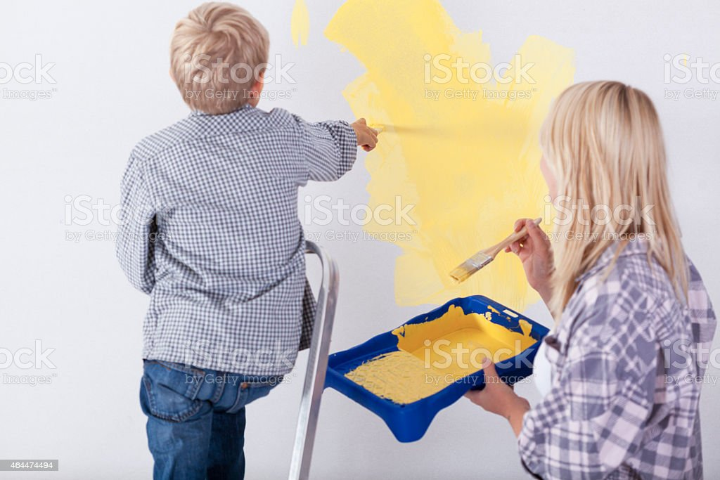 Little boy painting wall stock photo