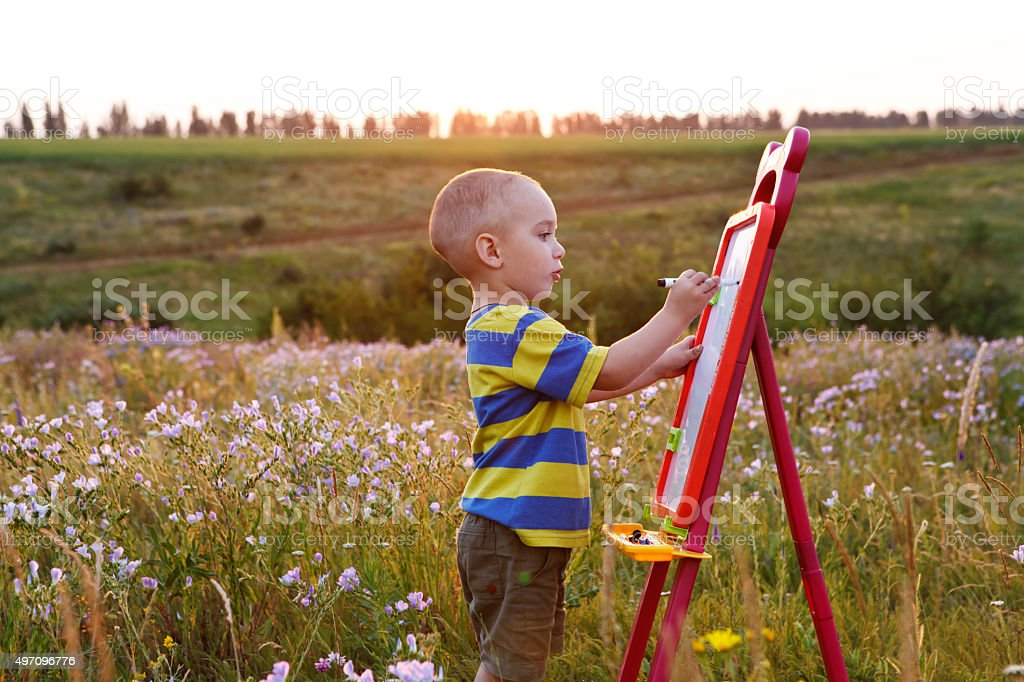 little boy paints on a canvas , landscape outdoors stock photo