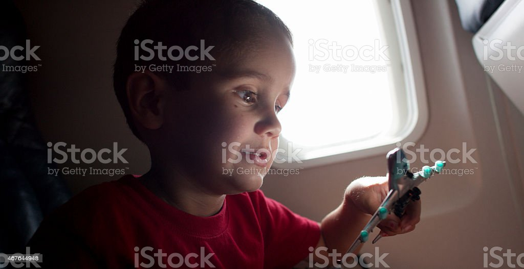 Little Boy Passing time on Airplane stock photo