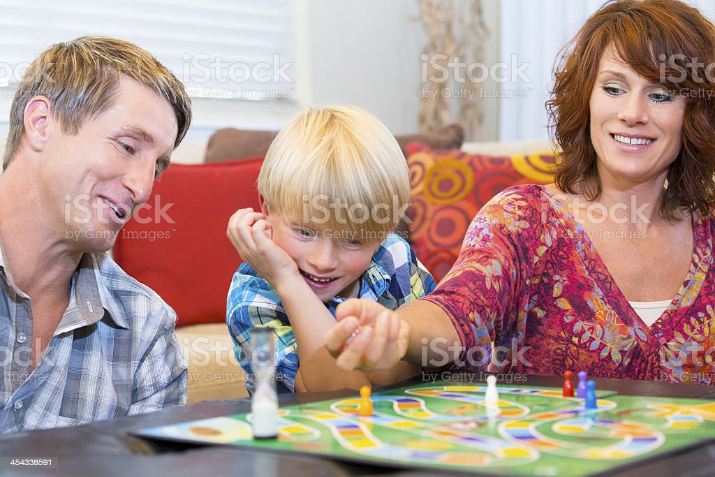 Little boy playing a fun board game with his parents stock photo