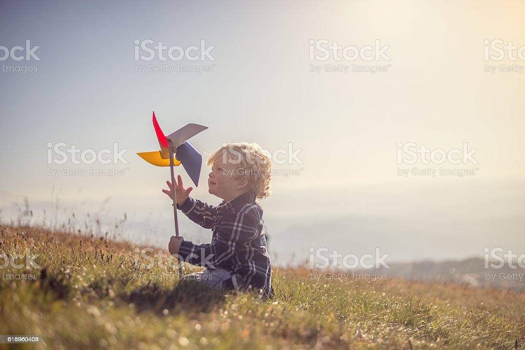 Little boy playing at the meadow stock photo
