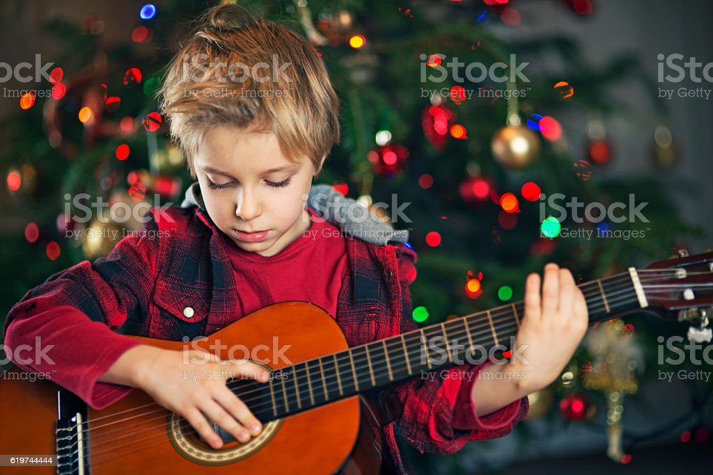 Little boy playing carols on guitar near the christmas tree stock photo