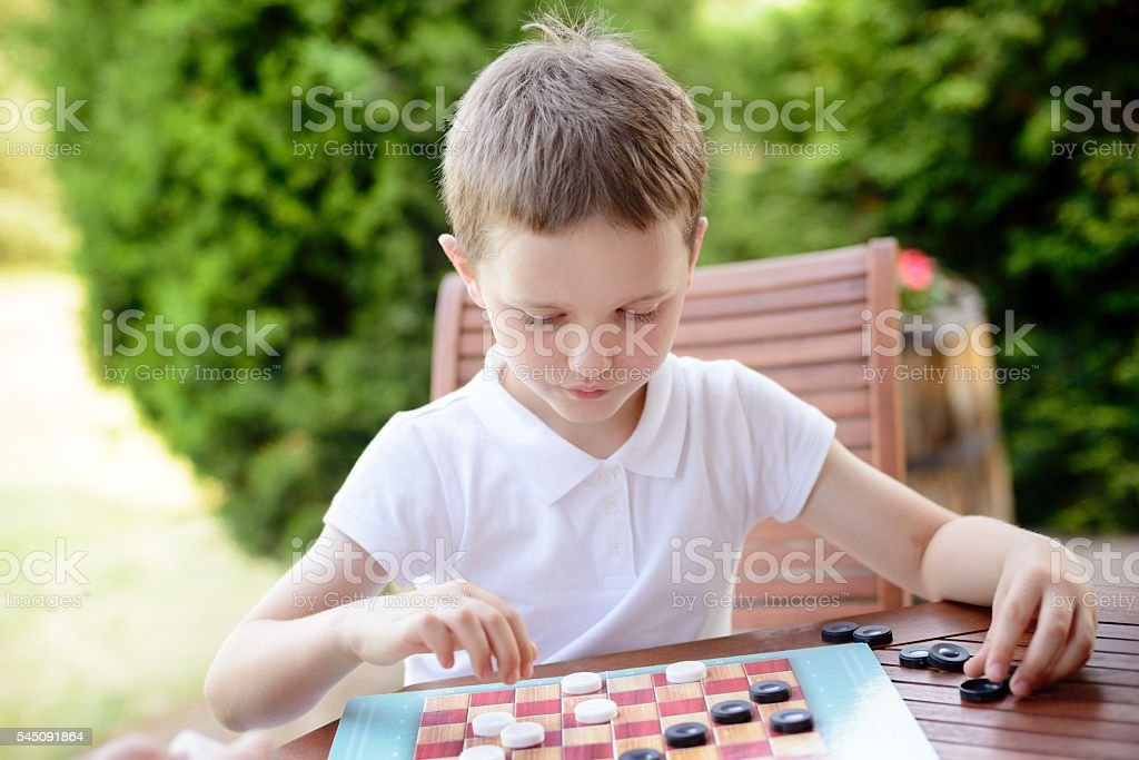 Little boy playing checkers board game stock photo
