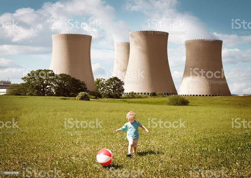 Little boy playing close to the nuclear plant stock photo