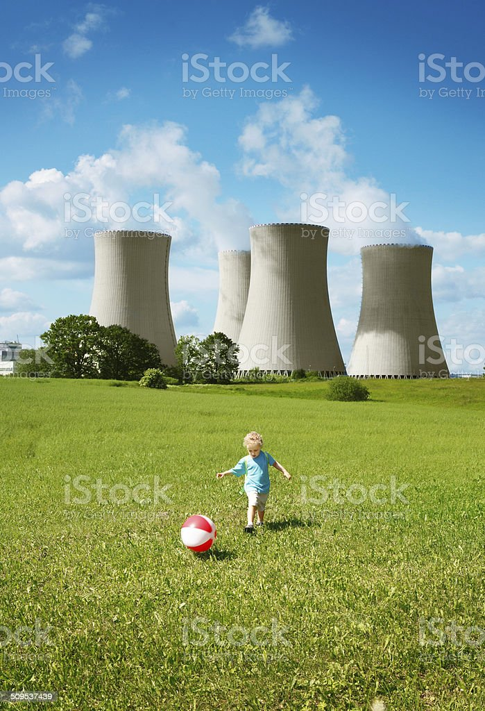 Little boy playing close to the nuclear power plant stock photo