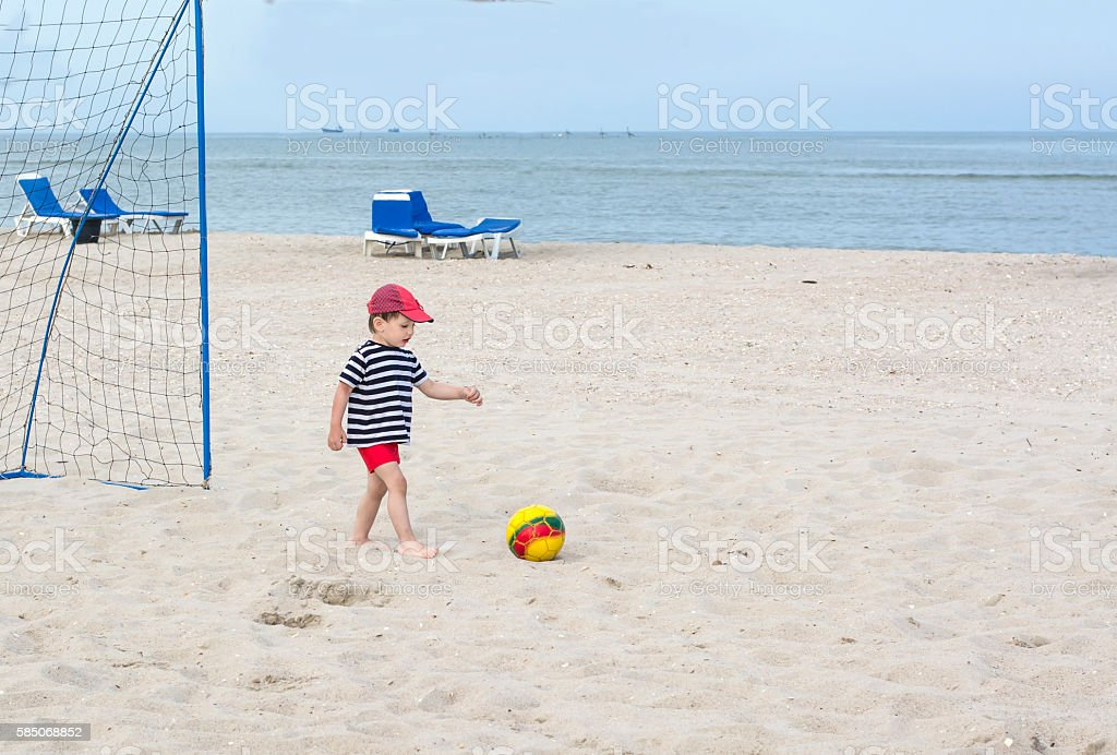Little boy playing football on the beach against the sea stock photo