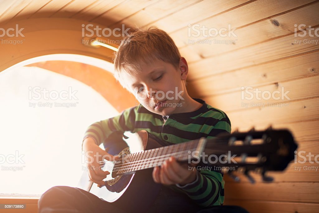 Little boy playing guitar near window stock photo