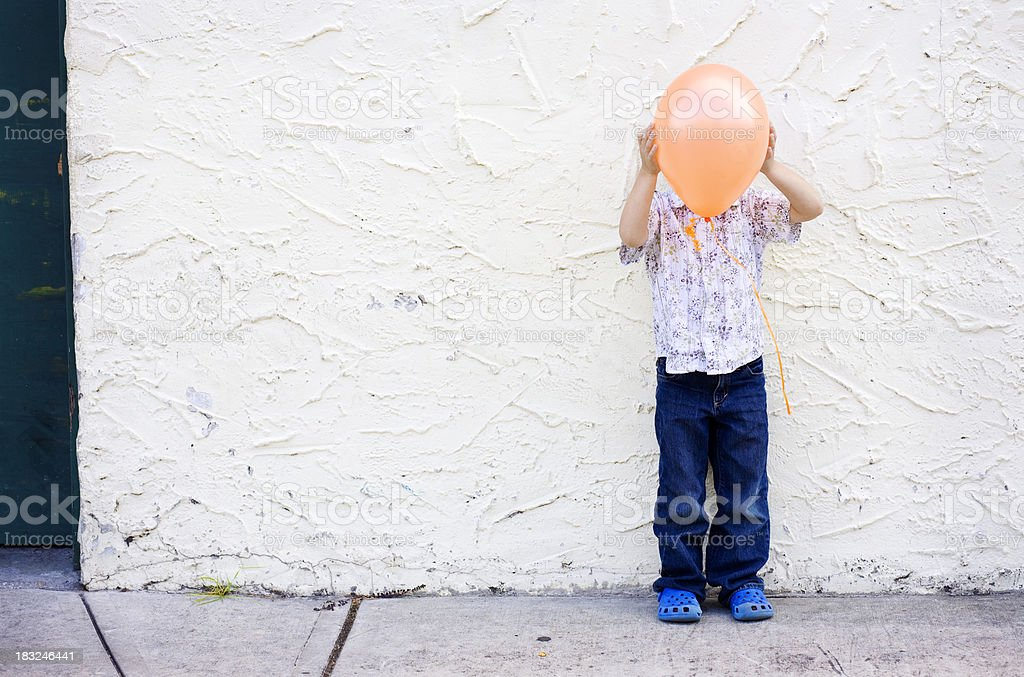 Little Boy Playing Hide and Seek with Balloon stock photo