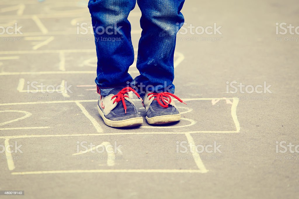 little boy playing hopscotch outdoors stock photo