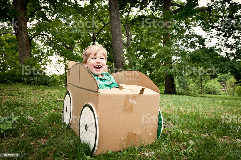A little boy playing in a cardboard car outside stock photo