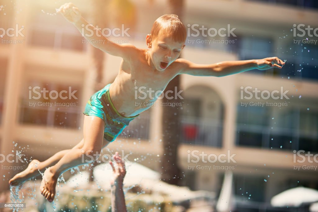 Little boy playing in resort pool stock photo
