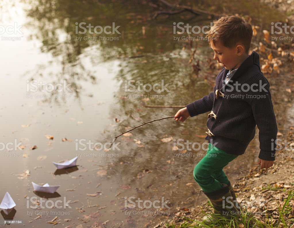 Little boy playing in river. stock photo