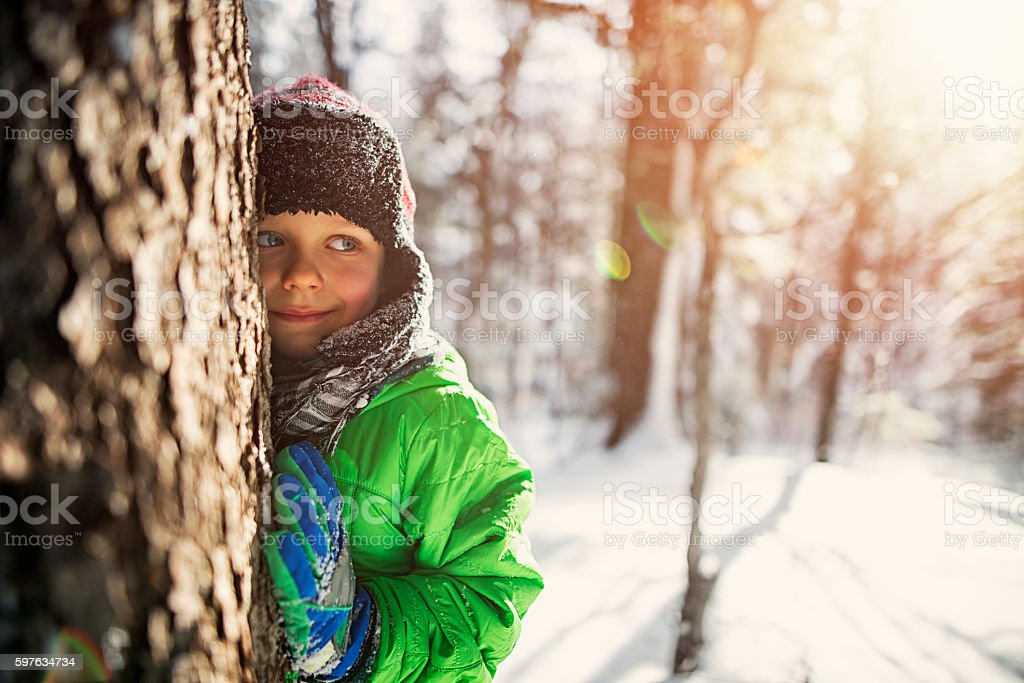 Little boy playing in sunny winter forest stock photo