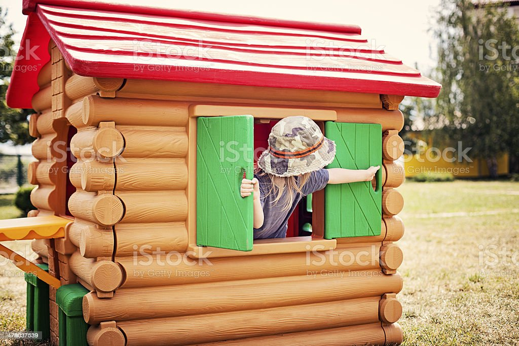 Little boy playing in the playhouse stock photo